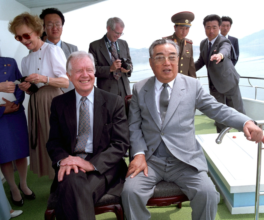 Jimmy Carter and Kim Il Sung sitting together, people behind them (© Korean Central News Agency/AP Images)