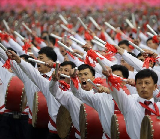 Rows of people in costume with arms raised (© AP Images)