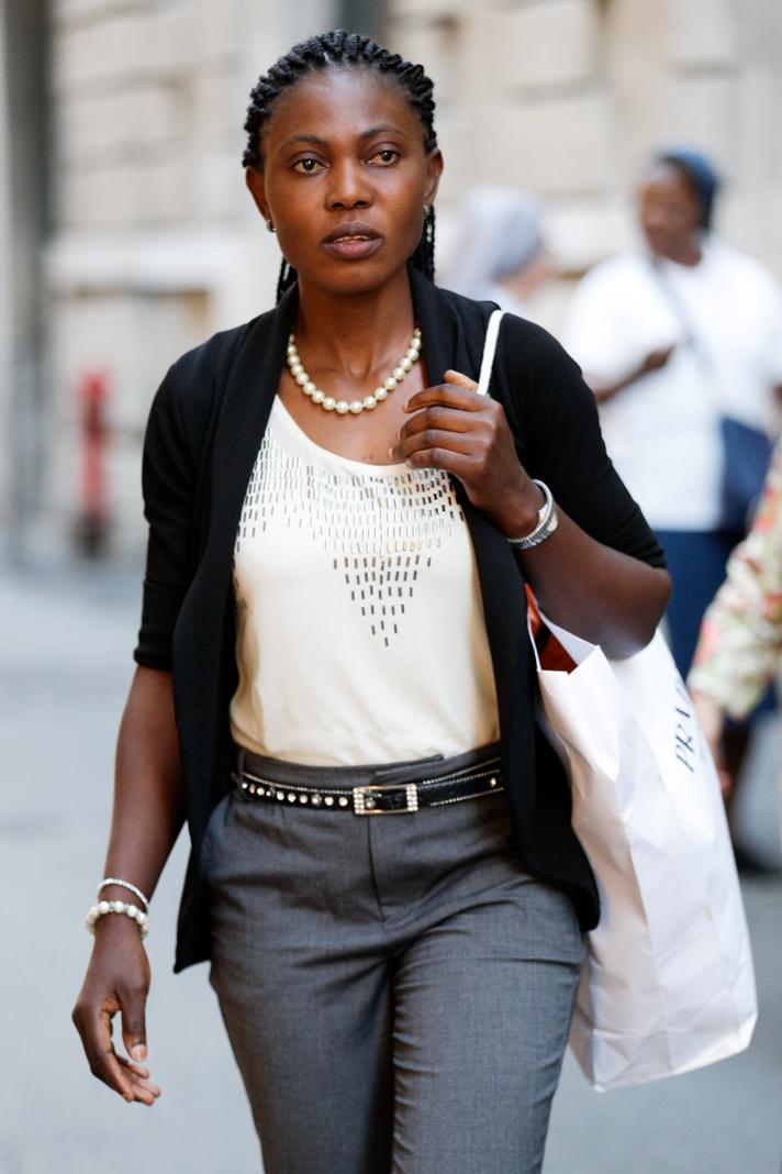 Woman walking on city sidewalk (© Andrew Medichini/AP Images)