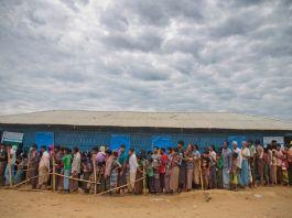 Fila de pessoas ao lado de um prédio (© A.M. Ahad/AP Images)