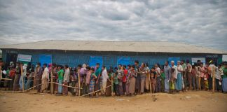 Line of people standing next to a building (© A.M. Ahad/AP Images)