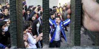 Crowd seen through bars (© File/AP Images)