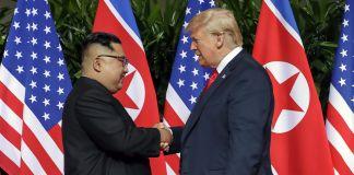 金正恩与特朗普总统在美国和北韩两国国旗前握手。 (© Evan Vucci/AP Images)
