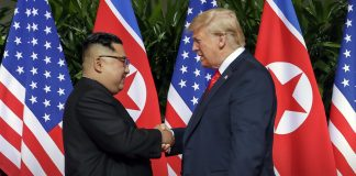 Kim Jong Un and President Trump shake hands in front of a number of U.S and North Korean flags (© Evan Vucci/AP Images)