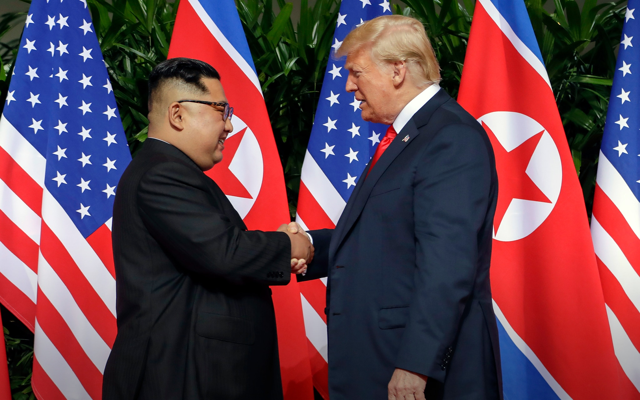 Kim Jong Un and President Trump shaking hands in front of U.S. and North Korean flags (© Evan Vucci/AP Images)