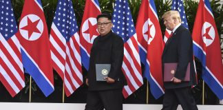 Kim Jong Un and President Trump walking and carrying documents (© Anthony Wallace/AP Images)