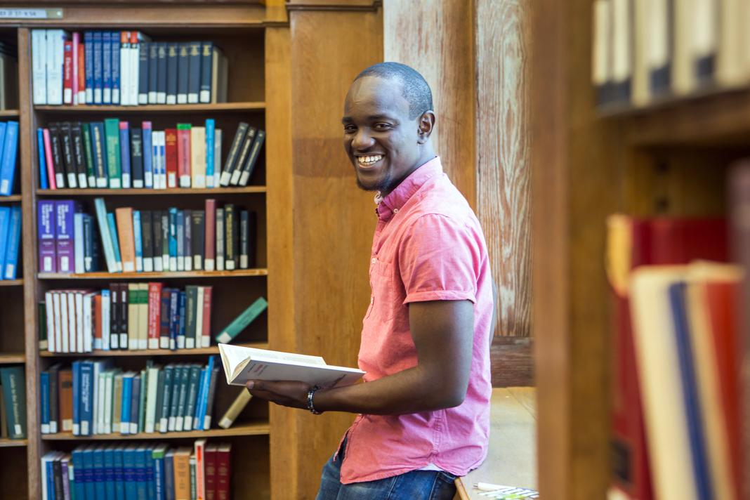 Студент в библиотеке с книгой в руках (State Dept./D.A. Peterson)