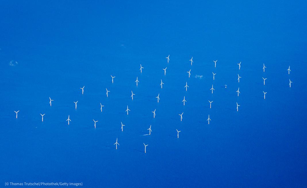 Vista aérea de turbinas eólicas em grande extensão de água (© Thomas Trutschel/Photothek/Getty Images)