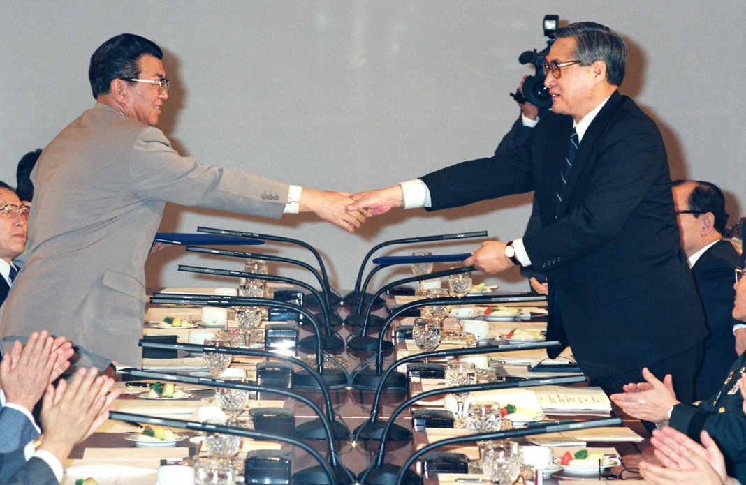 Two Korean leaders shaking hands across table (© Asahi Shumbun/Getty Images)