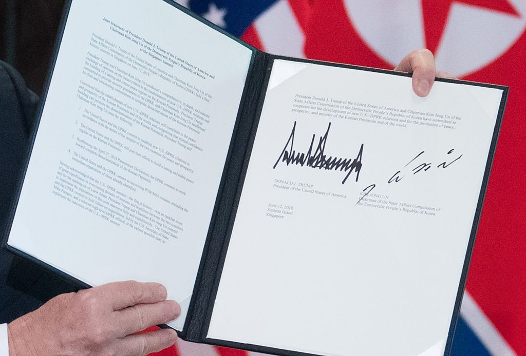 Hands holding up signed document (© Saul Loeb/AFP/Getty Images)