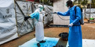 Man in protective clothing spraying another man in protective clothing with blue solution (Laura Stana/IMC)