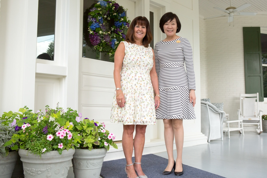 Two women standing on a porch in front of a house (State Dept./Allison Shelley)