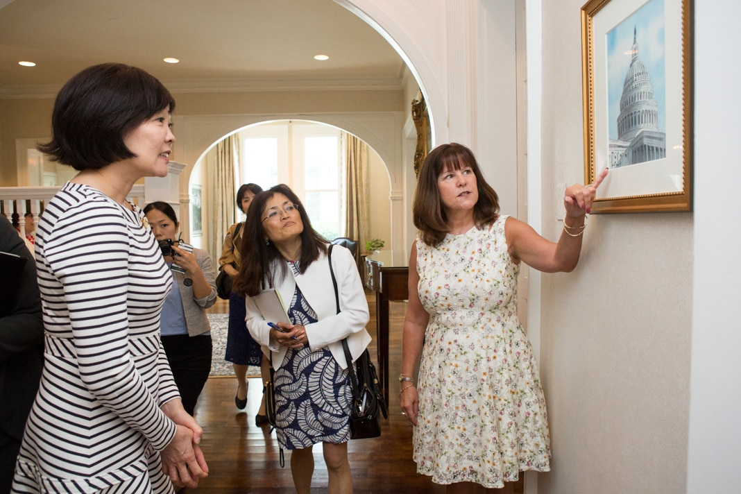 Woman showing others a painting of the U.S. Capitol building (State Dept./Allison Shelley)