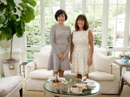 Two women standing in front of couch and next to small glass table set for tea (State Dept./Allison Shelley)