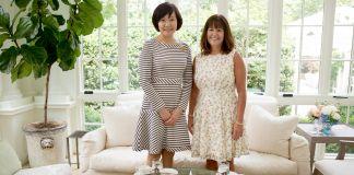 ソファを背にして、お茶のセットが置かれた小さなガラステーブルの前に立つ2人の女性(State Dept./Allison Shelley)