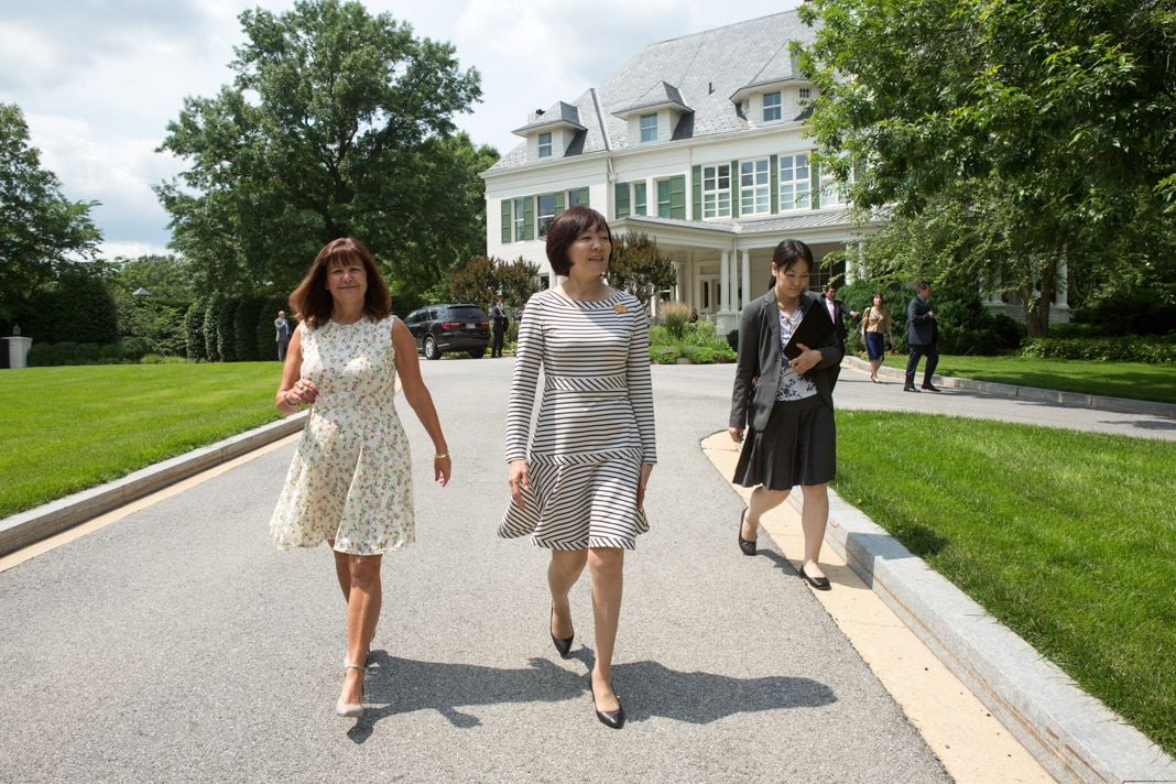 Three women walking down a driveway away from a house (State Dept./Allison Shelley)