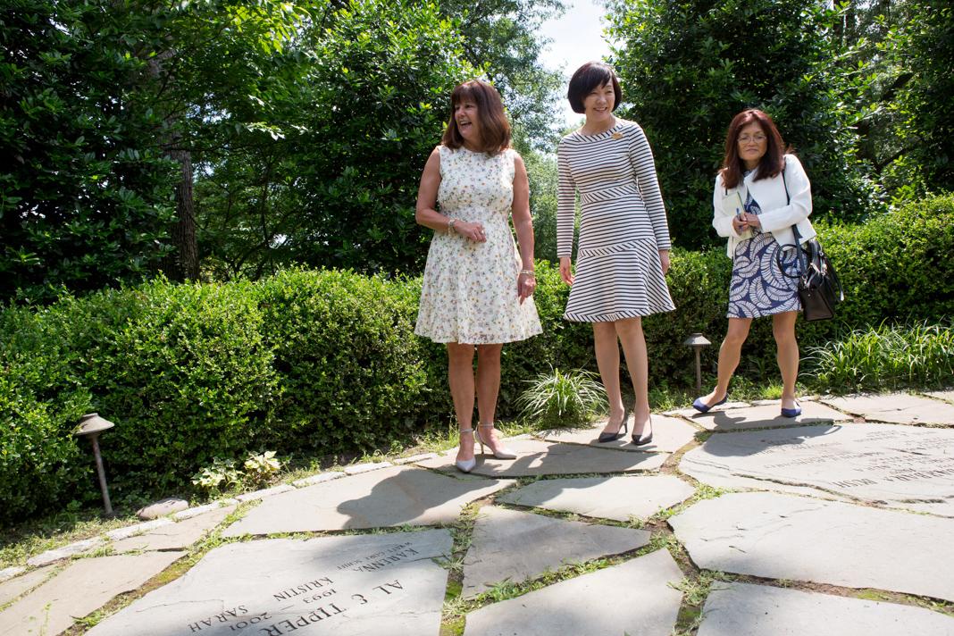 Three women standing on flagstone in a garden (State Dept./Allison Shelley)