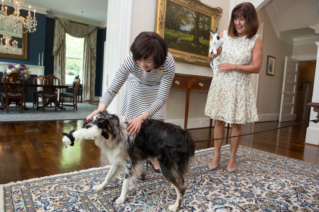 Woman playing with a dog as another woman holds a rabbit (State Dept./Allison Shelley)