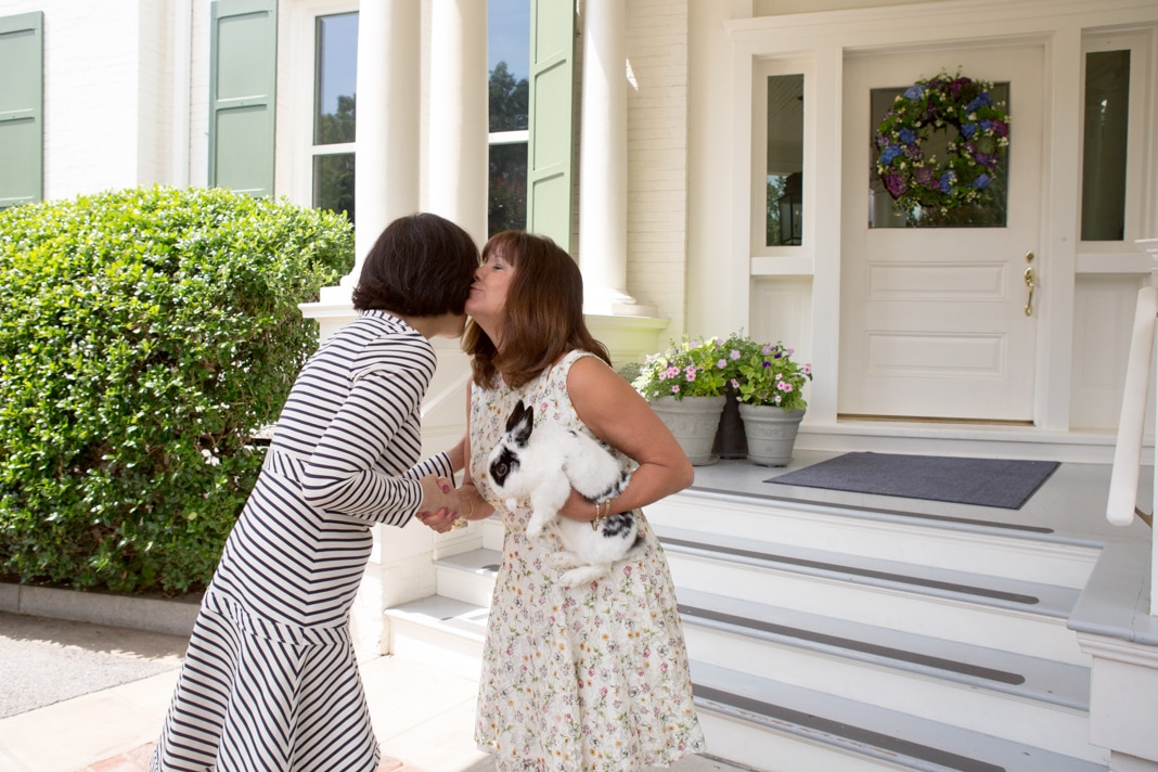 2 women kissing goodbye in front of a house (State Dept./Allison Shelley)