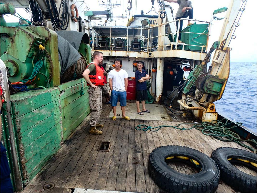 Personas de pie en la cubierta de un viejo barco pesquero (Guardia Costera de Estados Unidos/USCGC Kukui)