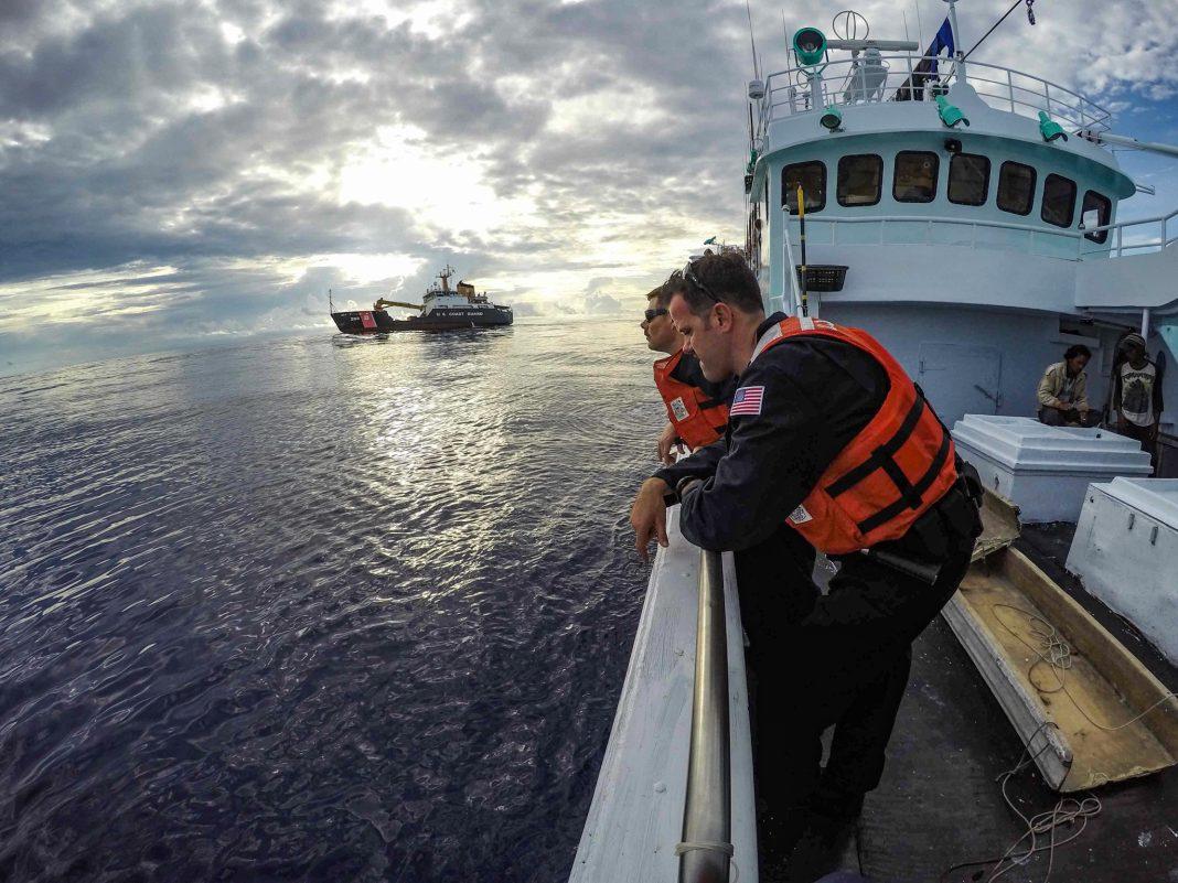 Dos personas apoyadas en la barandilla de un barco (Guardia Costera de Estados Unidos/Melissa E. McKenzie)