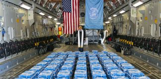Man standing behind 55 blue-covered caskets in belly of cargo plane (U.S. Army/Sergeant Quince Lanford)