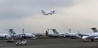 Aviões parados na pista e um decolando (© Vahid Salemi / AP Images)