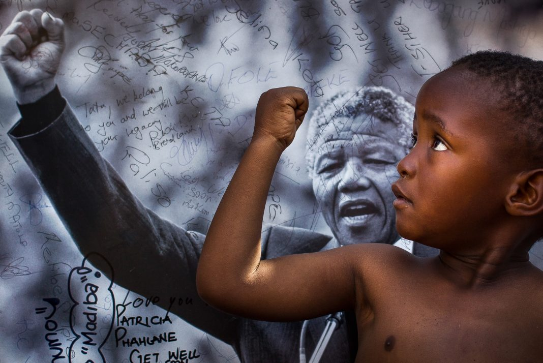 Young boy gesturing in front of picture of Nelson Mandela gesturing (© Ben Curtis/AP Images)