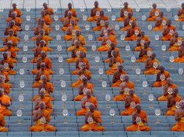 Pessoas com vestimenta cor laranja sentadas em fileiras (© Sakchai Lalit/AP Images)