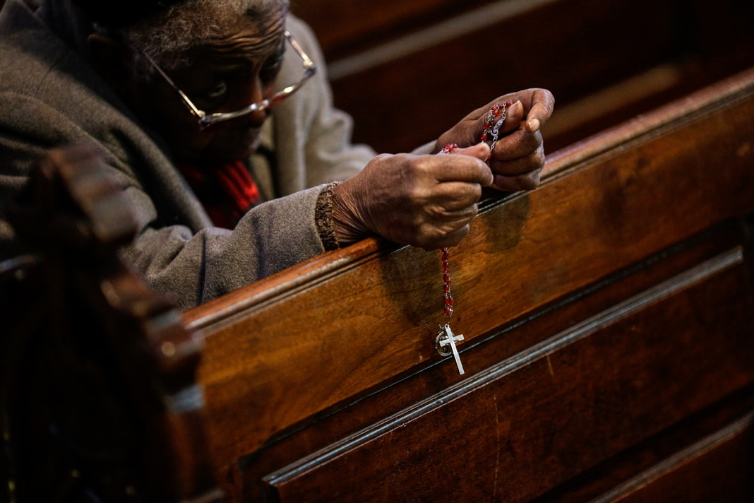 Person praying with rosary (© Patrick Semansky/AP Images)