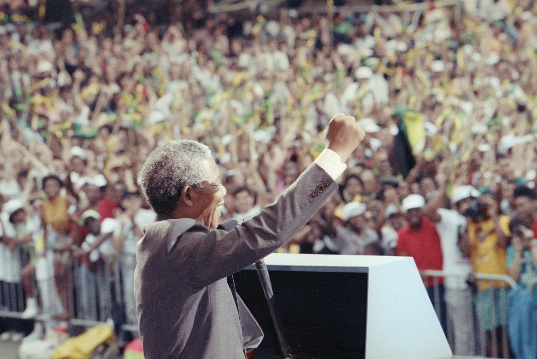 Nelson Mandela waving to crowd (© David Longstreth/AP Images)