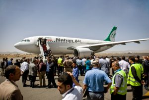 Airplane on tarmac surrounded by many people (© Hani Mohammed/AP Images)