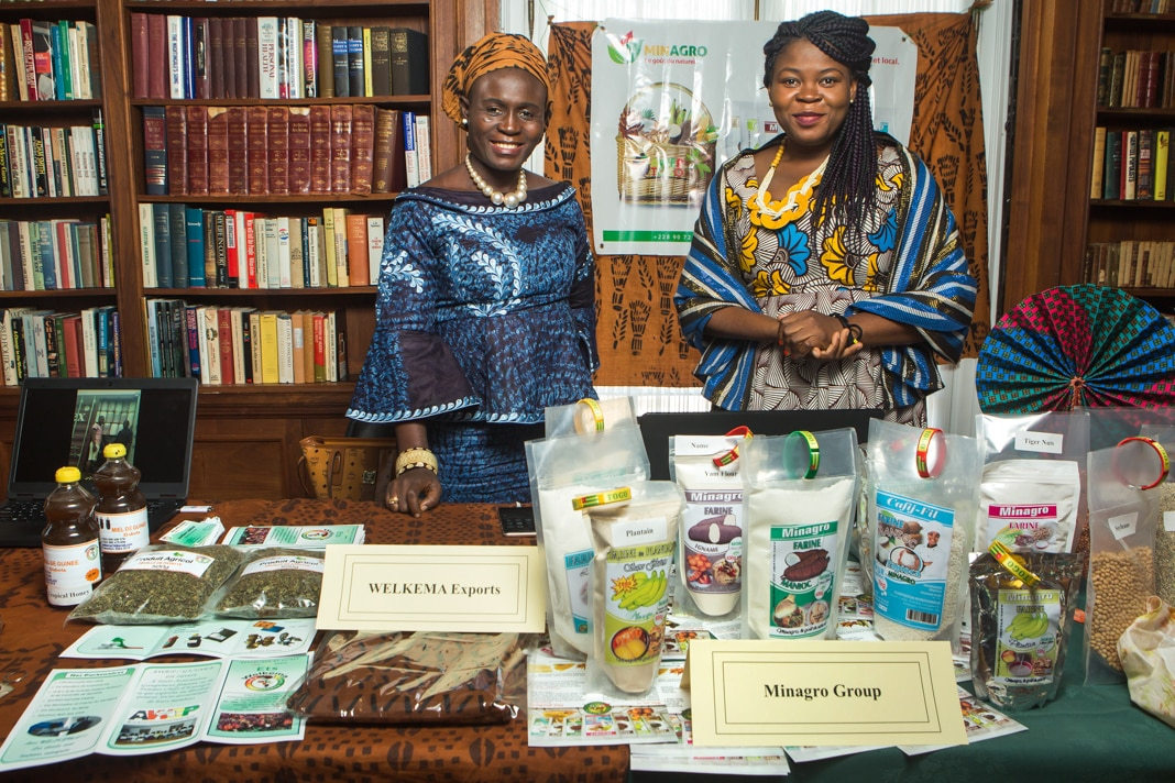 Two women standing behind a table displaying their wares (State Dept./D.A. Peterson)