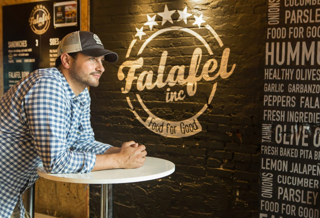Ahmad Ashkar leaning on a table, with Falafel Inc. logo painted on the wall behind him (State Dept./D.A. Peterson)