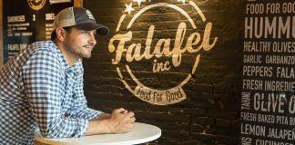Ahmad Ashkar accoudé sur une table haute, avec le logo de son restaurant peint sur le mur derrière lui (Département d'État/D.A. Peterson)