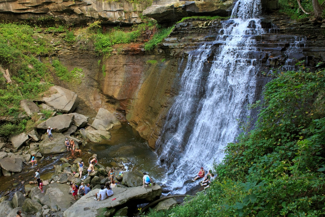 People sitting at the bottom of waterfall (© Daniel Borzynski/Alamy)