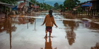 Woman walking down a flooded village street (© Jes Aznar/Getty Images)