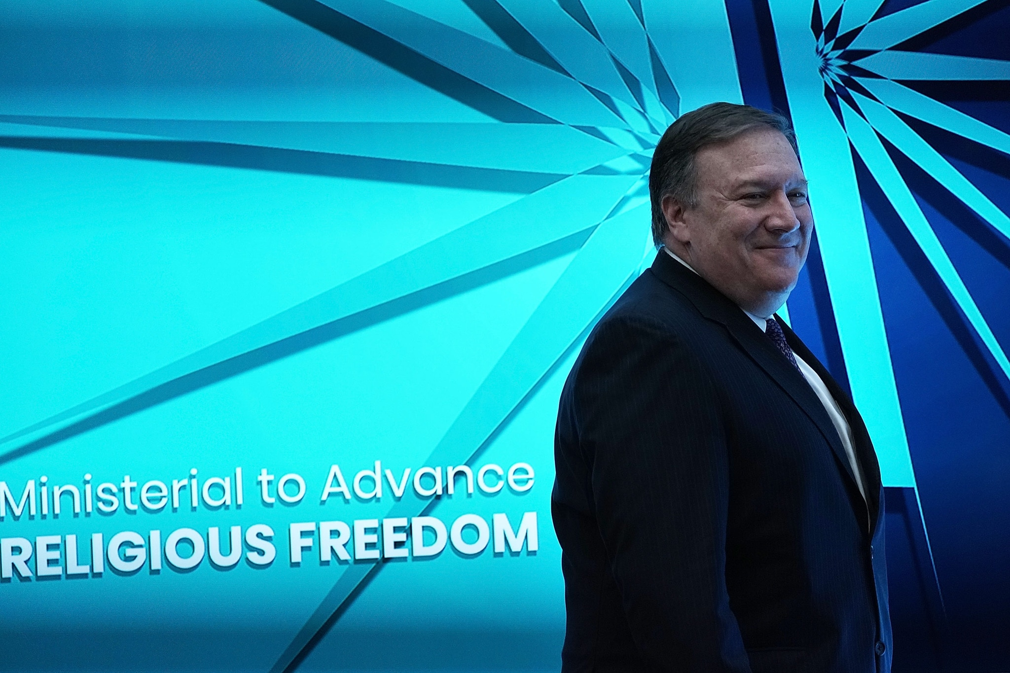Mike Pompeo, souriant, devant un mur sur lequel est écrit Ministerial to Advance Religious Freedom (@ Alex Wong/Getty Images)