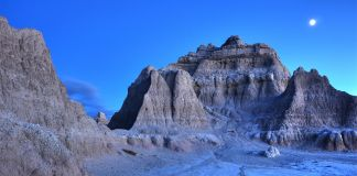 Photo des Badlands au Dakota du Sud, de nuit, avec la lune qui monte à l'horizon (© Daniel Regner/Getty Images)