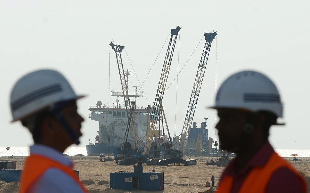 Two workers standing in front of pump dredging sand (© Lakruwan Wanniarachchi/AFP/Getty Images)