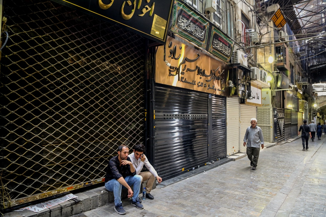 Two men sitting outside closed store in bazaar and few others walking past shuttered shops (© Fatemeh Bahrami/Anadolu Agency/Getty Images)