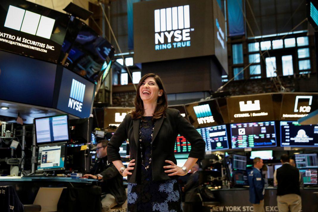 Wanita berdiri di ruangan besar dengan banyak monitor besar (© Brendan McDermid / Reuters)