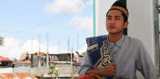 Un jeune homme vêtu d'un habit traditionnel philippin assis et regardant vers le ciel (USAID)