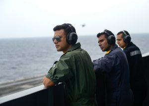 Three sailors wearing headphones lining ship railing (DOD/U.S. Navy Petty Officer 3rd Class Leon Wong)