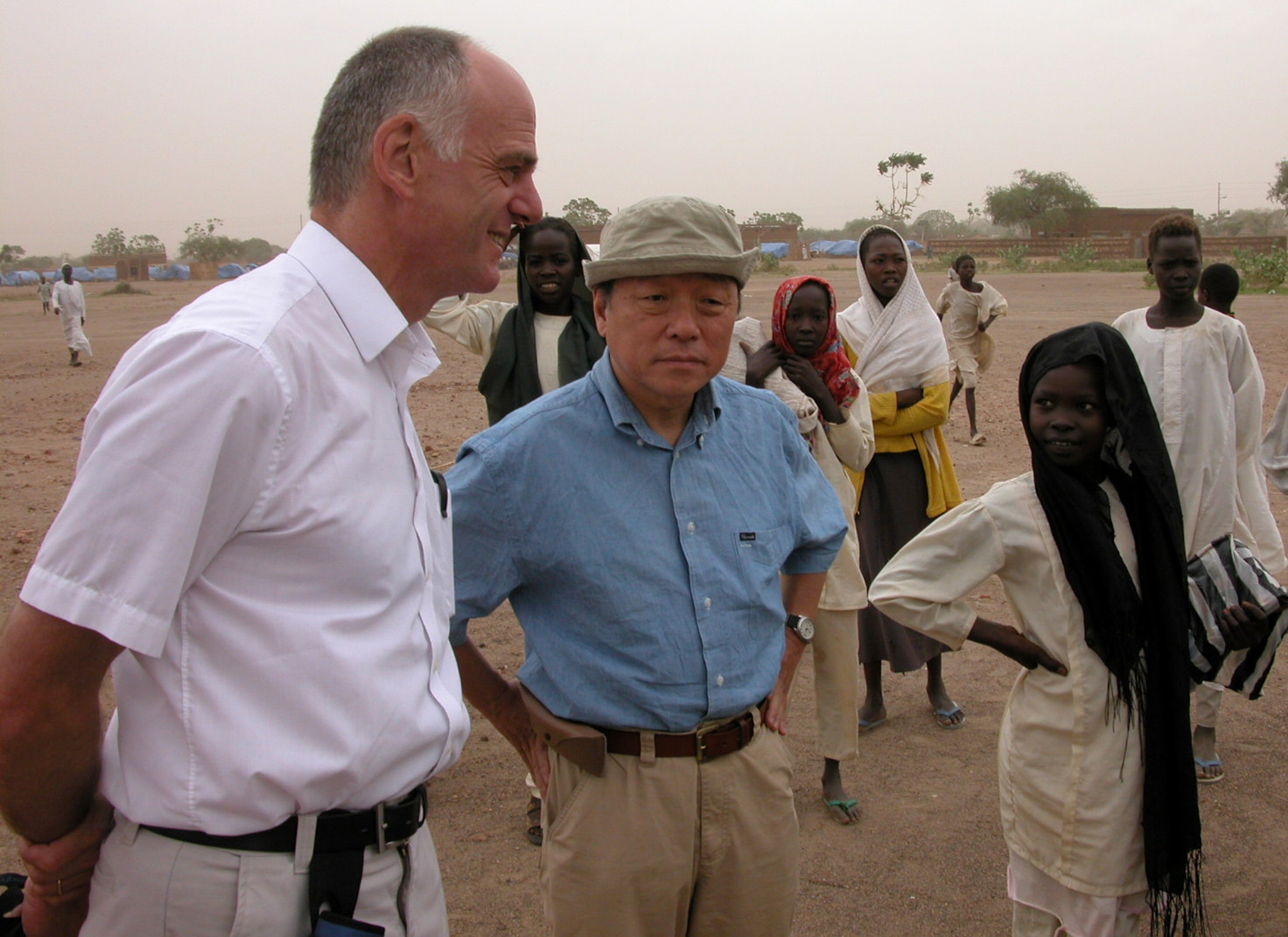 People standing in a dirt field talking (World Food Prize)