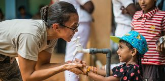 Une femme aidant une fillette à se laver les mains (U.S. Air Force Senior Airman Brittany A. Chase)