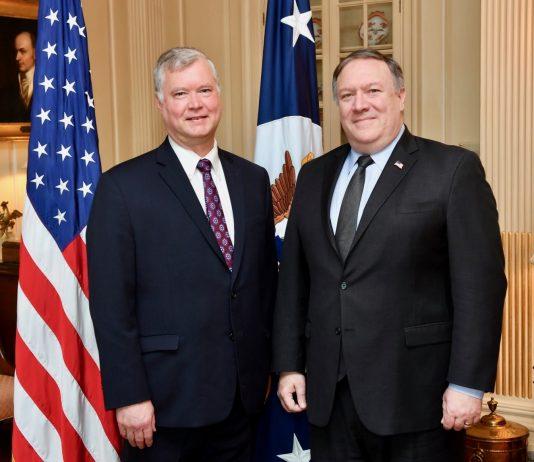 Stephen Biegun y Mike Pompeo de pie en un salón con banderas (Depto. de Estado)