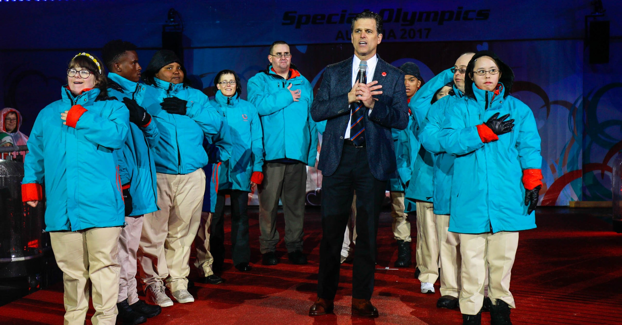 Man speaking, with athletes in winter gear around him (Special Olympics International)