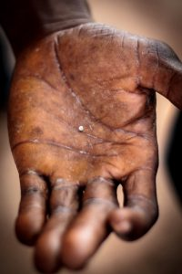 Open hand holding a small diamond (USAID/John Dwyer)