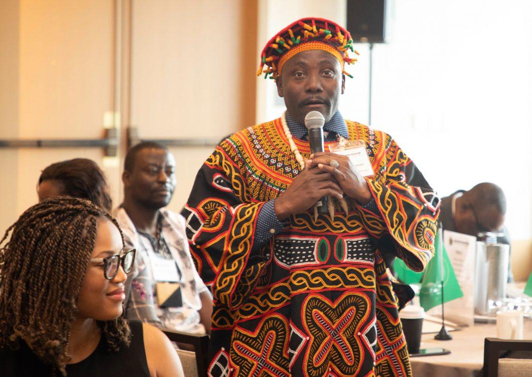 Man in African garb speaking into a microphone (© HK Media)